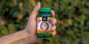 mão segurando pote com cápsulas de cranberry Kampo de Ervas